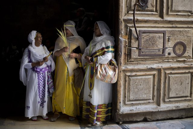 Orthodox Christian women hold palm fond's at the Church of the Holy Sepulcher, traditionally believed by many to be the site of the crucifixion and burial of Jesus Christ during Orthodox Palm Sunday, in Jerusalem, Sunday, April 5, 2015. Christians in the Holy Land and across the world are celebrating Easter, commemorating the day followers believe Jesus was resurrected in Jerusalem 2,000 years ago. (Photo by Ariel Schalit/AP Photo)