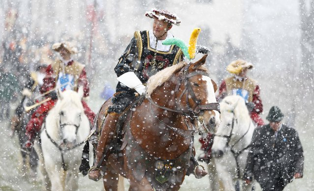 Local residents dressed in  historical costumes  ride  through heavy snowfall to get blessing for men and beast at the traditional Georg (St. George)  horse riding procession on Easter Monday in Traunstein, southern Germany, Monday, April 6, 2015. (Photo by Matthias Schrader/AP Photo)