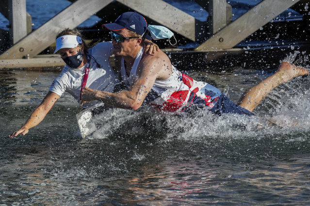 Great Britain's Hanna Mills is thrown at the water after winning the 470 women's gold medal at the Enoshima harbour during the 2020 Summer Olympics, Wednesday, August 4, 2021, in Fujisawa, Japan. (Photo by Bernat Armangue/AP Photo)