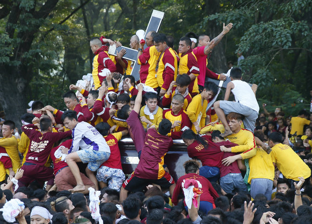 Filipino Roman Catholic devotees climb the carriage to kiss and rub with their towels the image of the Black Nazarene to celebrate its feast day Monday, January 9, 2017 in Manila, Philippines. The raucous celebration drew tens of thousands of devotees in a barefoot procession for several hours around Manila streets and end up with several people injured. (Photo by Bullit Marquez/AP Photo)