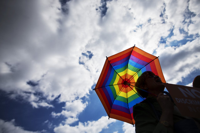 """Bobbie Paul, of Atlanta, holds a rainbow colored umbrella during a rally against a contentious """"religious freedom"""" bill, Tuesday, March 17, 2015, in Atlanta. The Georgia Senate gave decisive approval to the bill, one of a wave of measures surfacing in at least a dozen states that critics say could provide legal cover for discrimination against gays and transgender people. (Photo by David Goldman/AP Photo)"""