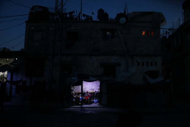 A Palestinian man sits as he sells vegetables in a makeshift shop lit with a lamp powered by a battery during a power cut in Beit Lahiya in the northern Gaza Strip January 11, 2017. (Photo by Mohammed Salem/Reuters)