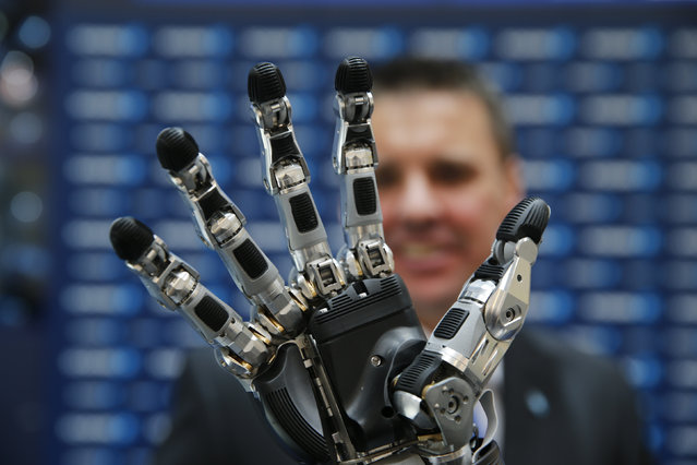 An employee presents the SCHUNK 5-finger anthropomorphic gripper hand at the world's largest industrial technology fair, the Hannover Messe in Hanover, April 12, 2015. (Photo by Wolfgang Rattay/Reuters)