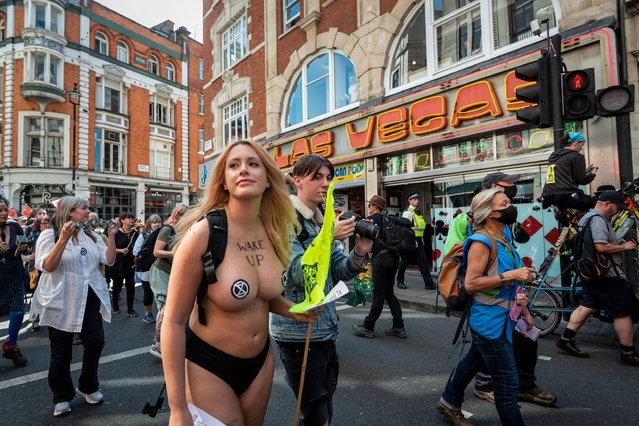 """A topless climate activist Laura Amherst, 31, from Extinction Rebellion protests in Soho, London, United Kingdom on August 25, 2021. The event is part of the """"Impossible Rebellion"""" protest to """"target the root cause of the climate and ecological crisis"""" and are ongoing for two weeks until the Government agrees to stop all new fossil fuel investments. (Photo by Stephen Chung/Alamy Live News)"""