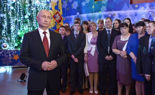 Russian President Vladimir Putin, left, and guests wait during a recording of his annual televised New Year's message to the nation during a New Year dinner celebration in Khabarovsk, Russia's Far East, Tuesday, December 31, 2013. (Photo by Alexei Nikolsky/AP Photo/RIA-Novosti/Presidential Press Service)