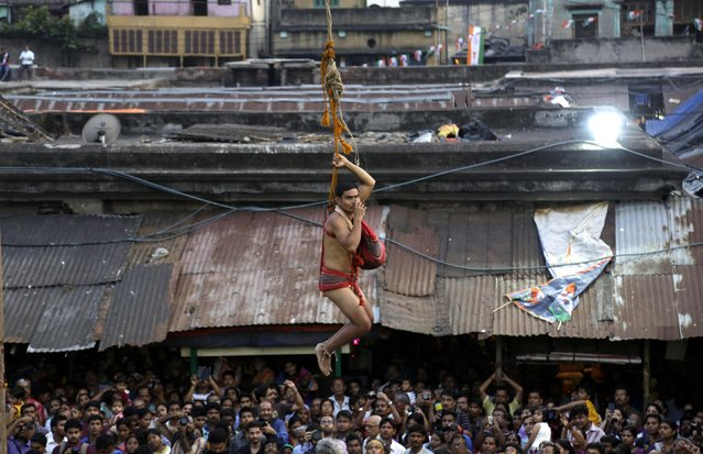 A Hindu devotee offers a prayer before swinging on a rope tied to a pole during Shiva Gajan festival or Charak on the last day of Bengali calendar in Kolkata, India, Tuesday, April 14, 2015. Faithful Hindu devotees offer various such rituals each year in the hope of winning the favor of Hindu god Shiva and ensuring the fulfillment of their wishes. (Photo by Bikas Das/AP Photo)