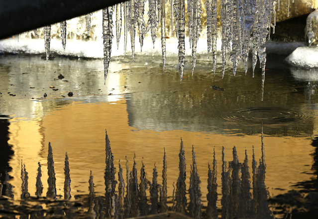 The walls of nearby buildings are reflected in a partially frozen fountain, Wednesday, January 4, 2017, in Tacoma, Wash. Wet winter weather slammed much of the West on Wednesday, with storms dropping several inches of snow on one Oregon city and several feet of the white stuff predicted high in the Sierra Nevada. (Photo by Ted S. Warren/AP Photo)