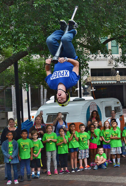 XPogo athlete Ryan O'Malley flips in the air during his extreme pogo demonstration in Hemming Park, in Jacksonville, Fla., Thursday, April 16, 2015. (Photo by Bob Mack/The Florida Times-Union via AP Photo)