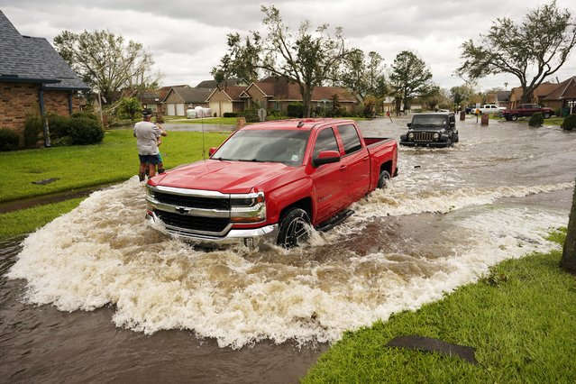 Vehicles pass through a flooded street after Hurricane Ida moved through Monday, August 30, 2021, in LaPlace, La. (Photo by Steve Helber/AP Photo)