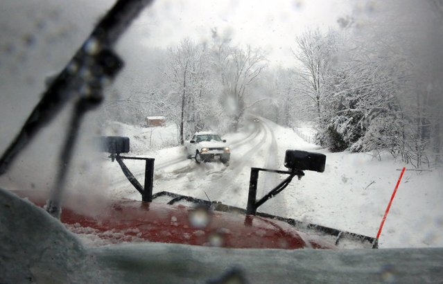 A truck is stopped on Mt. Tabor Rd., as a Monroe County Highway Department truck clears snow, Sunday, January 5, 2014, in Ellettsville, Ind. (Photo by Jeremy Hogan/AP Photo/Bloomington Herald-Times)