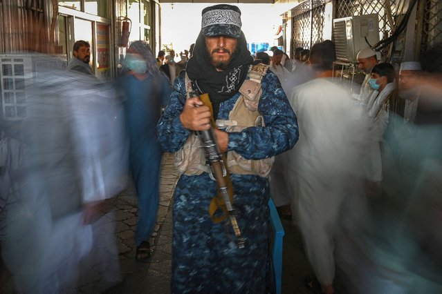 A Taliban fighter stands guard as people move past him at a market with shops dealing with currency exchange in Kabul on September 5, 2021. (Photo by Aamir Qureshi/AFP Photo)
