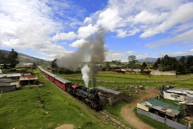 """A """"La Sabana"""" tourist train steam locomotive manufactured in 1934 crosses farmland in La Caro village near Bogota, March 8, 2015. (Photo by Jose Miguel Gomez/Reuters)"""