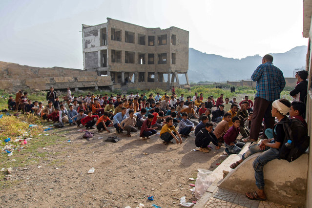Yemeni students attend class in their destroyed school compound on the first day of the new academic year in the country's third-city of Taez on August 30, 2021. (Photo by Ahmad Al-Basha/AFP Photo)