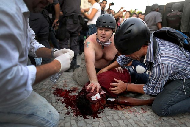 Cameraman Andrade Santiago is helped after he was injured during violent clashes with police during a protest against a bus fare increase in Rio de Janeiro, on February 6, 2014. It was not clear if the journalist was hit by a homemade explosive thrown by protesters or a stun grenade shot by police. (Photo by Leo Correa/Associated Press)