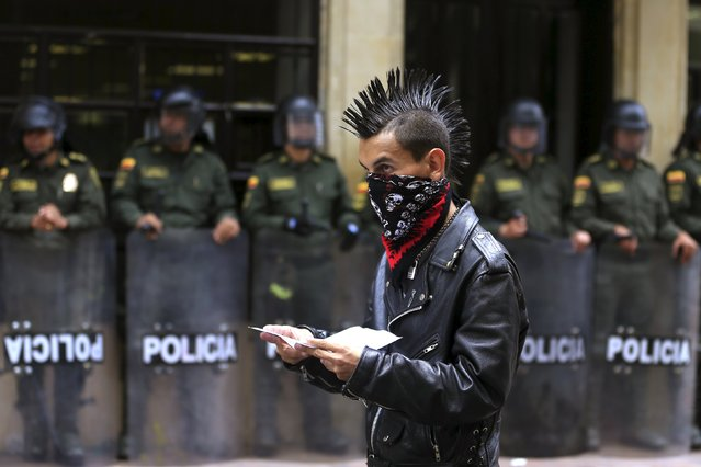 A demonstrator walks in front riot policemen during protests for Labor Day in Bogota, Colombia May 1, 2015. (Photo by Jose Miguel Gomez/Reuters)