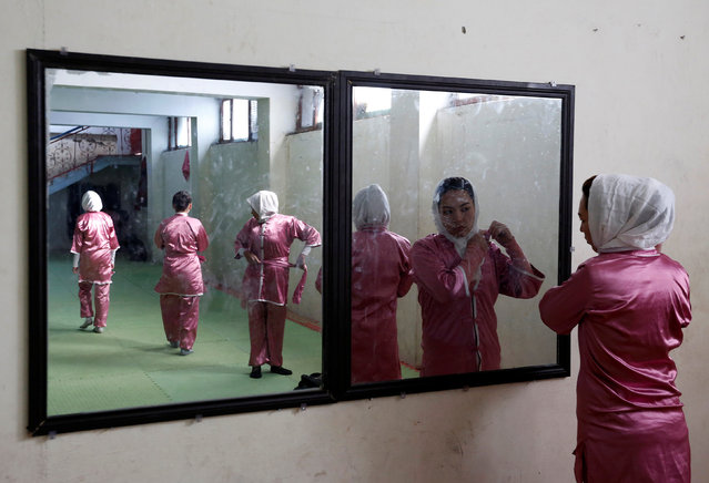 Hatifa Rezai (R), 19, a student of the Shaolin Wushu club, is reflected in a mirror as she adjusts her scarf before her exercise in Kabul, Afghanistan January 19, 2017. (Photo by Mohammad Ismail/Reuters)