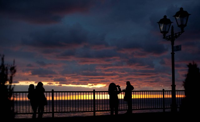 People, some taking pictures, watch the sun set over the Black Sea ahead of the 2014 Winter Olympics, Thursday, February 6, 2014, in Sochi, Russia. (Photo by Peter Dejong/AP Photo)