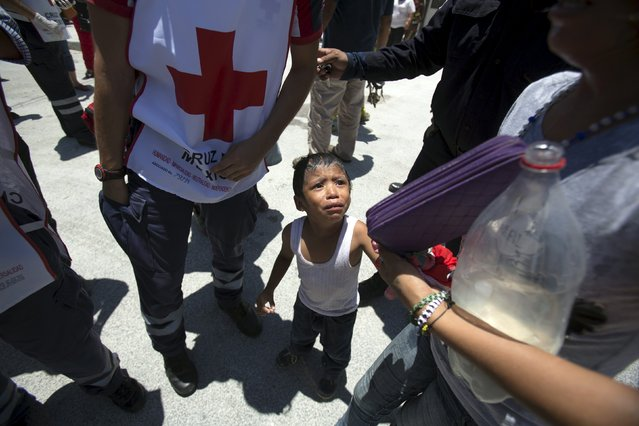 A child experiencing shock is seen next to a Red Cross paramedic outside the jail during a clash of rival groups in the prison of Cancun, Mexico April 26, 2015. (Photo by Victor Ruiz Garcia/Reuters)