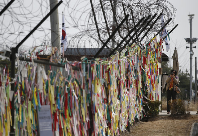 A woman takes a picture near the ribbons hanging on a wire fence to pray for the reunification of the two Koreas at the Imjingak Pavilion near the border with North Korea, in Paju, South Korea, Friday, March 18, 2016. North Korea defied U.N. resolutions by firing a medium-range ballistic missile into the sea on Friday, Seoul and Washington officials said, days after its leader Kim Jong Un ordered weapons tests linked to its pursuit of a long-range nuclear missile capable of reaching the U.S. mainland. (Photo by Lee Jin-man/AP Photo)