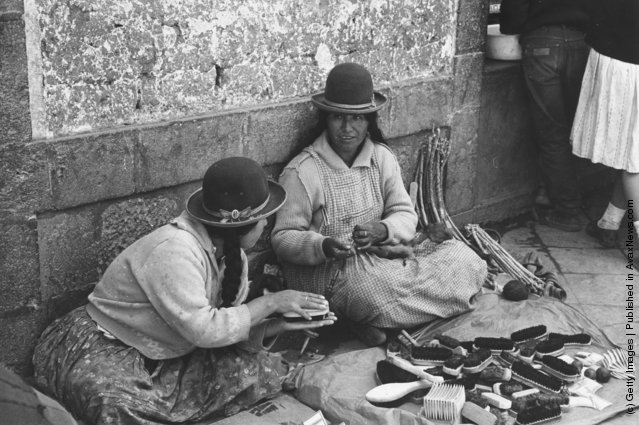 Two Peruvian Indian women, wearing traditional bowler-style hats, sell home-made brushes in a street market, 1955