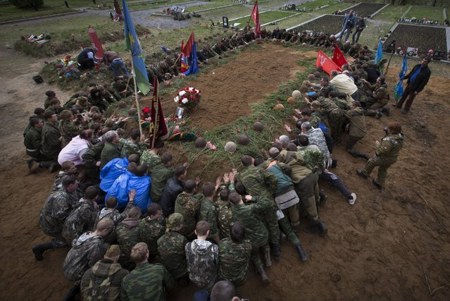 In this photo taken Thursday, May 7, 2015 photo, members of volunteer search teams observe a minute of silence during a reburial ceremony of remains of Soviet soldiers killed during World War II,  at the Sinyavino Heights memorial near the village of Sinyavino, 50 km (31 miles) east of  St. Petersburg, Russia. (Photo by Dmitry Lovetsky/AP Photo)
