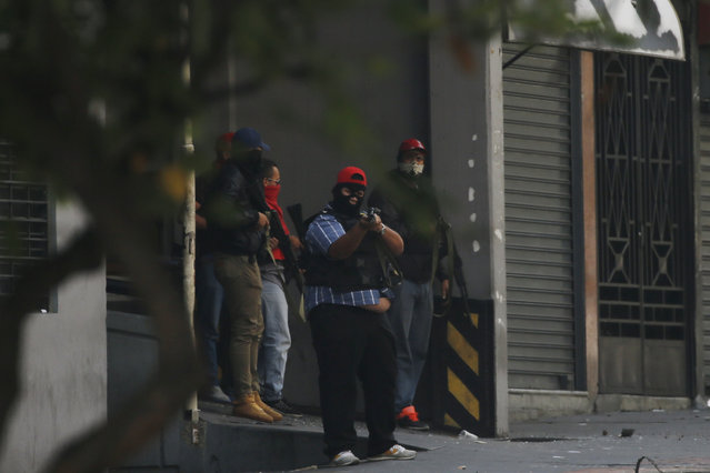Armed and masked supporters of President Nicolas Maduro stand at an entrance of the Transportation Ministry in Caracas, Venezuela, Tuesday, April 30, 2019, during a military uprising attempt to oust Maduro. (Photo by Fernando Llano/AP Photo)