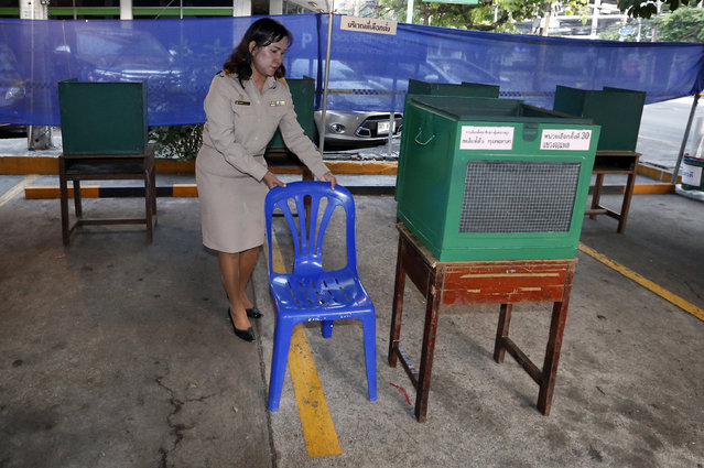 A Thai officer adjusts a chair before the voting for the general election at a polling station in Bangkok, Thailand, Sunday, March 24, 2019. Thailand's first general election since the military seized power in a 2014 coup is scheduled to be held on Sunday. (Photo by Sakchai Lalit/AP Photo)
