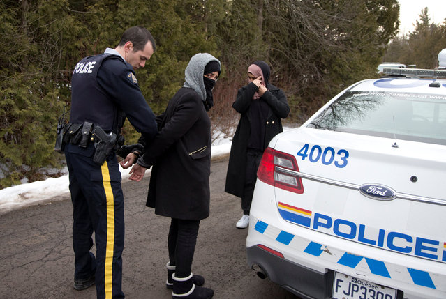 Two women claiming to be from Yemen are detained by a Royal Canadian Mounted Police (RCMP) officer after crossing the U.S.-Canada border into Hemmingford, Quebec, Canada February 22, 2017. (Photo by Christinne Muschi/Reuters)