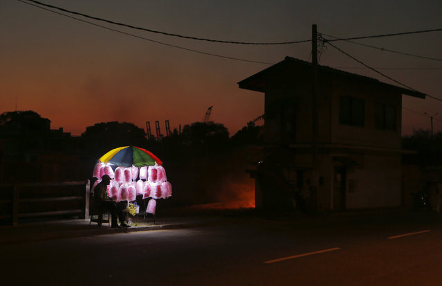 A Sri Lankan candy floss vendor awaits customers by a road side at dusk as light emits from burning garbage from behind an adjacent house, right, in Colombo, Sri Lanka, Sunday, April 3, 2016. The Colombo Port is seen silhouetted far behind. (Photo by Eranga Jayawardena/AP Photo)