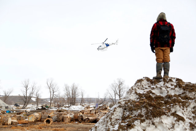 A protester watches a law enforcement helicopter circle the main opposition camp against the Dakota Access oil pipeline near Cannon Ball, North Dakota, U.S., February 23, 2017. (Photo by Terray Sylvester/Reuters)