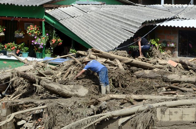 A man clears rubble from the ruins of his house, after a landslide sent mud and water crashing onto homes in the municipality of Salgar in Antioquia department May 18, 2015. (Photo by Reuters/Stringer)