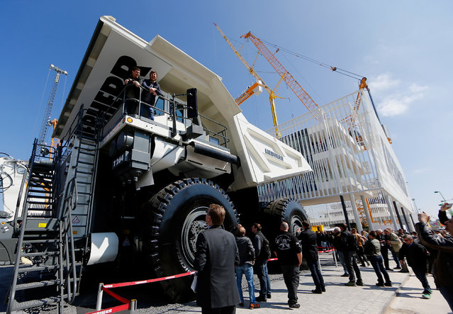 """Visitors look at a giant dump truck at the """"Bauma"""" Trade Fair for Construction, Building Material and Mining Machines and Construction Vehicles and Equipment in Munich, southern Germany, April 11, 2016. (Photo by Michael Dalder/Reuters)"""