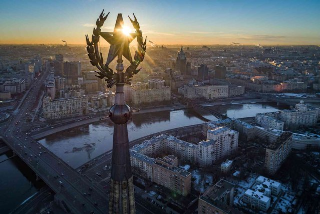 In this photo taken on Thursday, March 7, 2019, the sun rises over the star on the spire on top of a Stalin-era skyscraper, now the Radisson Royal Hotel on the banks of the Moskva River in Moscow, Russia. (Photo by Dmitry Serebryakov/AP Photo)