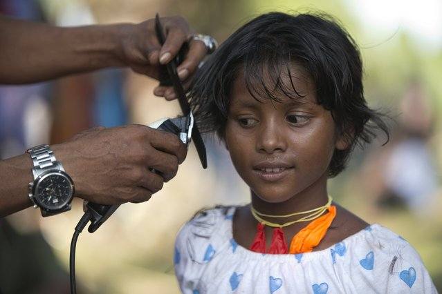 A young Rohingya migrant, who arrived in Indonesia this week by boat, has her hair cut by a volunteer at a temporary shelter in Aceh Timur regency, near Langsa in Indonesia's Aceh Province May 24, 2015. (Photo by Darren Whiteside/Reuters)