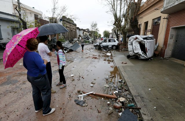 People look on as debris is seen along a street in Dolores, the day after the city was hit by a tornado, April 16, 2016. (Photo by Andres Stapff/Reuters)