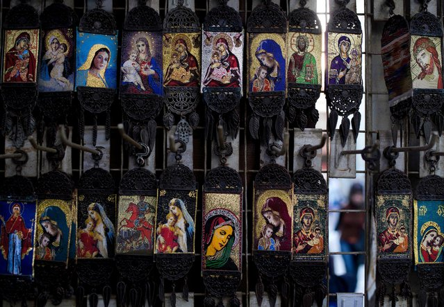 In this Saturday, April 16, 2016 photo, Christian icons depicting the Virgin Mary and Jesus Christ are displayed in a shop outside the historic 7th century Umayyad Mosque, that was built on the site of a Christian basilica, in Damascus, Syria. The mosque is and one of the oldest and largest mosques in the world and an adjacent mausoleum contains the tomb of medieval Muslim Sultan Saladin. (Photo by Hassan Ammar/AP Photo)