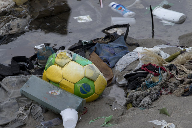 A soccer ball decorated in the colors of Brazil's national flag lays strewn along the shore with other trash in Guanabara Bay in Rio de Janeiro, Brazil, Monday, June 1, 2015. With poor trash and sewage services, Rio's waterways are choked with raw sewage and garbage, which university art students used to create an exhibition to draw attention to the fetid state of the citys bay. (AP Photo/Silvia Izquierdo)