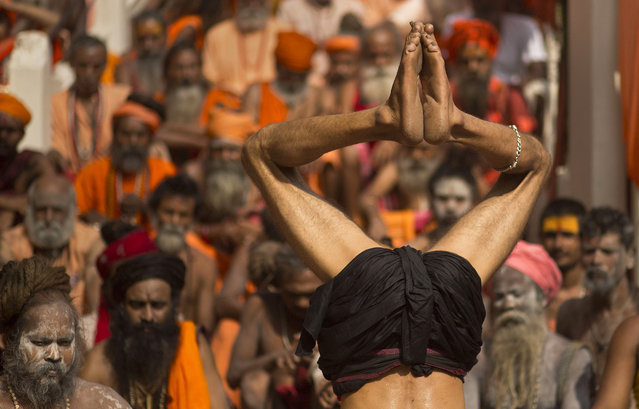 An Indian Sadhu, or Hindu holy man, performs a yoga position on International Yoga Day at Kamakhya temple in Gauhati, India, Friday, June 21, 2019. (Photo by Anupam Nath/AP Photo)