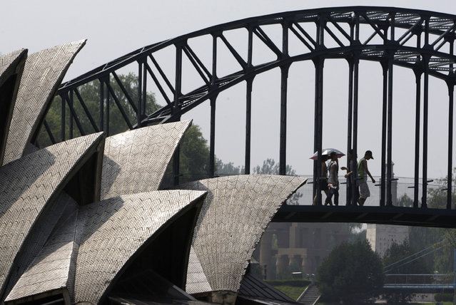 Visitors to Beijing's World Park walk across a replica of the Sydney Harbour Bridge situated next a replica of the Sydney Opera House in Beijing July 16, 2008. (Photo by David Gray/Reuters)