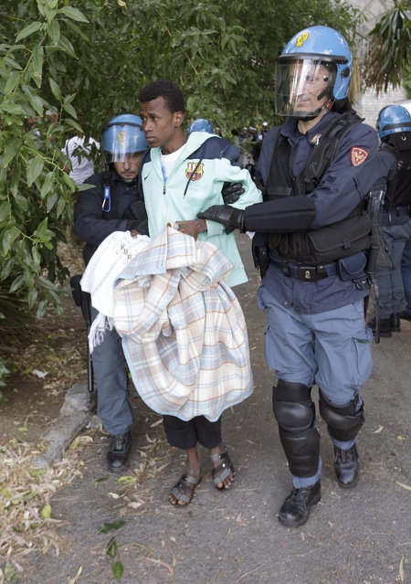 A migrant is evacuated by Italian police at the Franco-Italian border near Menton, southeastern France, Tuesday, June 16, 2015. Some 150 migrants, principally from Eritrea and Sudan, have been trying since last Friday to cross the border from Italy but have been blocked by French and Italian police. (AP Photo/Lionel Cironneau)