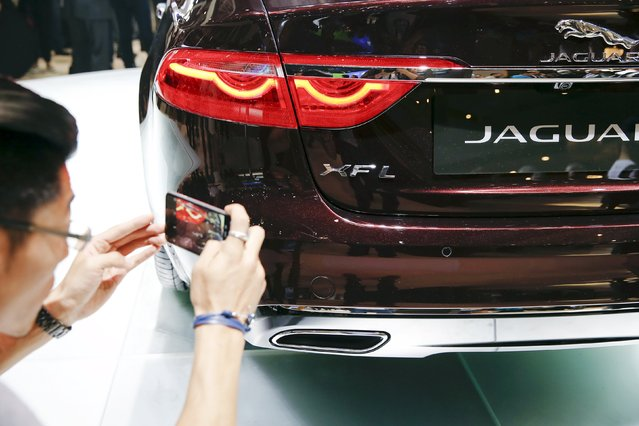 A visitor takes pictures of newly unveiled Jaguar XFL during the Auto China 2016 auto show in Beijing April 25, 2016. (Photo by Damir Sagolj/Reuters)