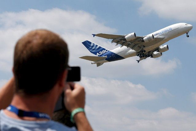 A visitor take a picture of an Airbus A380, the world's largest jetliner, during a flying display during the 51st Paris Air Show at Le Bourget airport near Paris, June 17, 2015. REUTERS/Pascal Rossignol