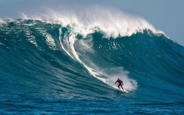 A surfer catches a wave at Dungeons, a famous surfing spot, close to Hout Bay, in Cape Town, on July 26, 2019. This spot, which produces some of South Africa's biggest waves, needs a variety of conditions like wind, swell size, wave period and direction, that often follows storms, to produce huge waves on an offshore reef, which attracts and challenges the surfers. (Photo by Rodger Bosch/AFP Photo)