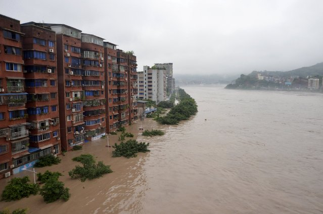 Residential buildings are seen partially submerged by an overflowing river after heavy rainfall hit Dazhou, Sichuan province, China, June 25, 2015. The National Meteorological Center (NMC) issued a yellow alert for rainstorms on Tuesday evening. Heavy downpour is expected to sweep at least 10 provinces in China, Xinhua News Agency reported. (Photo by Reuters/Stringer)