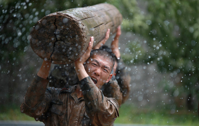 Armed police carry a log during a drill amid the scorching summer heat on July 30, 2019 in Yangzhou, Jiangsu Province of China. (Photo by Meng Delong/VCG via Getty Images)