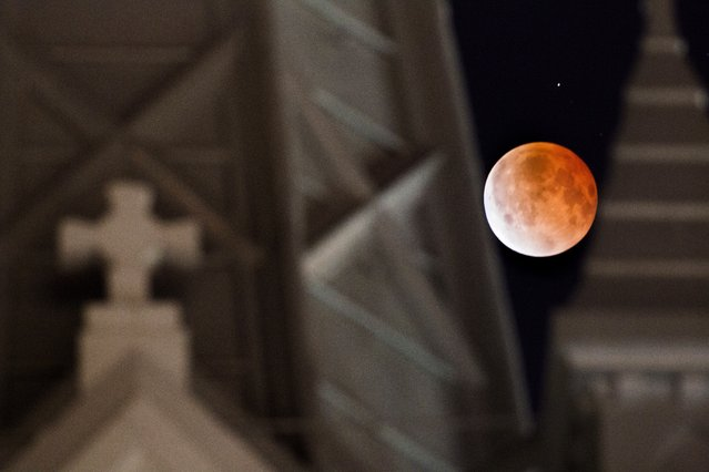 The moon glows a red hue during a lunar eclipse as it is framed between the steeples on the Annunciation Catholic Church in Houston, Tuesday, April 15, 2014. Tuesday's eclipse is the first of four total lunar eclipses that will take place between 2014 to 2015. (Photo by Johnny Hanson/AP Photo/Houston Chronicle)
