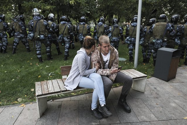 A couple sit in a boulevard as police walk to prevent protesters during a rally in Moscow, Russia, Saturday, August 10, 2019. Tens of thousands of people rallied in central Moscow for the third consecutive weekend to protest the exclusion of opposition and independent candidates from the Russian capital's city council ballot. (Photo by AP Photo/Stringer)