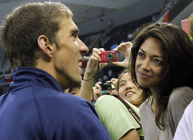 In this July 29, 2011 file photo, U.S. swimmer Michael Phelps talks to his girlfriend Nicole Johnson, right, after the medal ceremony for the men's 4x200 Freestyle Relay, at the FINA Swimming World Championships in Shanghai, China. The 18-time Olympic gold medalist and fiancé Nicole Johnson welcomed Boomer Robert Phelps on Thursday night, May 5, 2016, in Arizona, where Phelps has been training in preparation for the upcoming Rio Olympics. (Photo by Wong Maye-E/AP Photo)