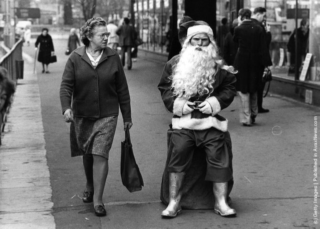 1975: A woman casts a sceptical glance at a rather surly looking man dressed as Santa in a busy shopping street