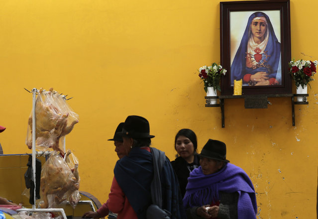 In this June 7, 2015 photo, women walk past an altar dedicated to Our Lady of Sorrows, as they enter a market in Pujili, Ecuador. (Photo by Dolores Ochoa/AP Photo)